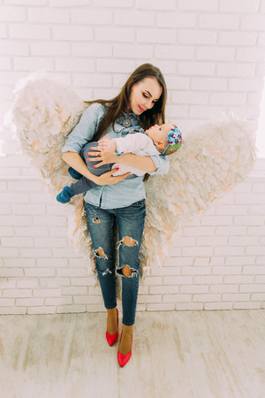 The full-length portrait of the woman with angle wings holding the little baby at the background of the white brick wall. Stok Fotoğraf
