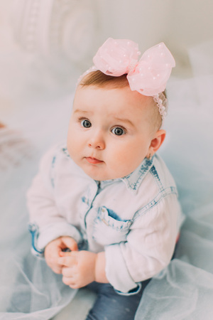 Lovely baby with the bow on the head is covered into the tulle and sitting on the floor. The close-up above portrait. Stok Fotoğraf