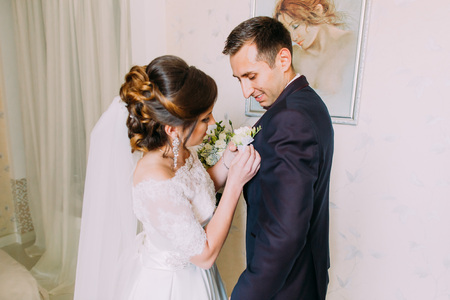 Wedding preparation. Bride is putting the boutonniere on the jacket of the smiling groom. Stok Fotoğraf
