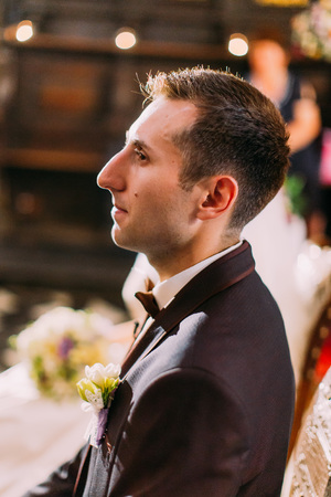 The close-up side portrait of the serious groom sitting on the chair during wedding ceremony in the church. Stok Fotoğraf