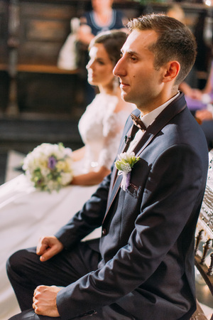 The half-length side portrait of the groom sitting on the chair during wedding ceremony in the church at the blurred background of the bride. Stok Fotoğraf