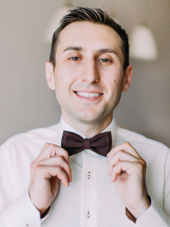 Close-up portrait of the cheerful groom correcting his brown bow-tie.