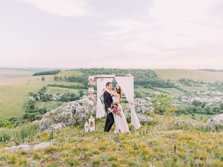 Horizontal photo of the hugging newlywed couple near the lovely decorated wedding arch placed in the mountains. Banque d'images