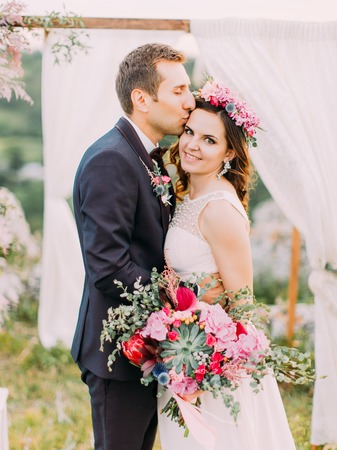 Close-up outdoor portrait of the cheerful groom kissing the smiling bride in the forehead near the arch. Standard-Bild