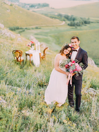 Lovely hugging newlyweds at the background of the wedding table in the mountains. Banque d'images