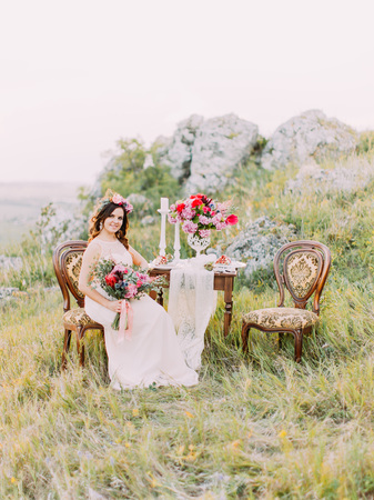 The beautiful bride with the bouwuet is sitting on the antique chair near the wedding table in the mountains.
