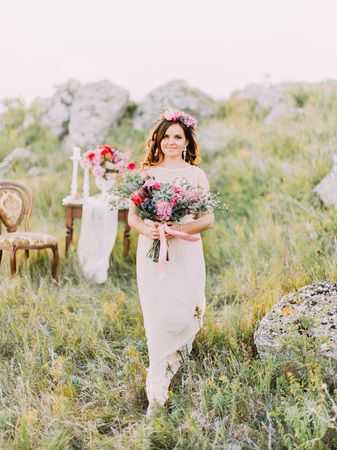 Full-length view of the beautiful bride with the wedding bouquet walking in the mountains.