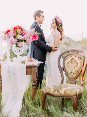 The vertical view of the hugging newlyweds behind the blurred wedding table set. Banque d'images - 106216528