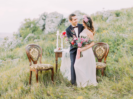 Happy newlyweds are spending time in the mountains. The composition of the wedding table set.