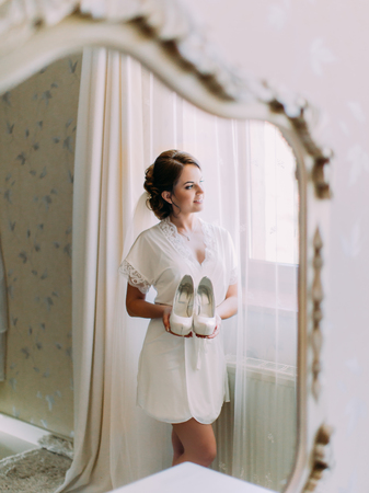 Lovely bride is holding the wedding shoes while looking through the window. The reflection in the mirror. Standard-Bild