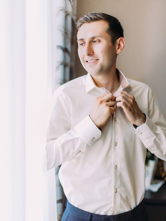 The happy groom is buttoning his shirt while looking through the window. Banque d'images