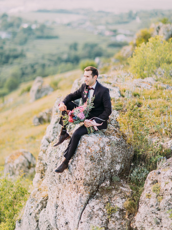 The side view of the groom sitting on the rock and holding the huge bouquet of colourful flowers. Standard-Bild