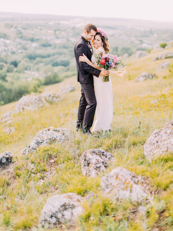Full-length view of the hugging newlyweds standing on the mountains. The groom is holding the bouquet.
