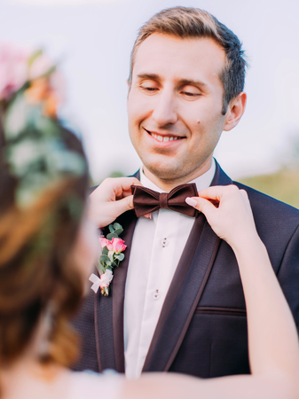 The close-up view of the smiling groom. The bride is correcting the bow-tie. Standard-Bild