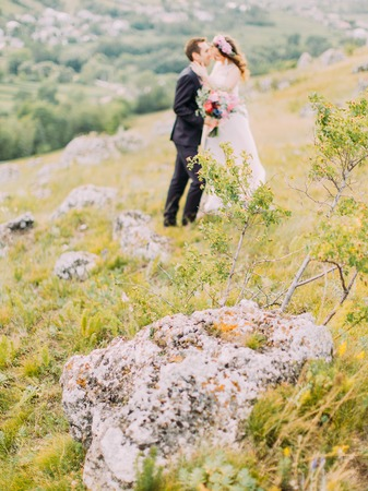 The close-up view of the huge rock at the blurred background of the kissing newlyweds. Stok Fotoğraf - 108050168