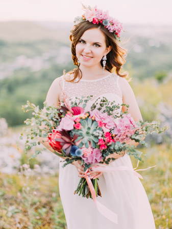 Lovely cheerful bride is holding the colourful huge wedding bouquet in the mountains.