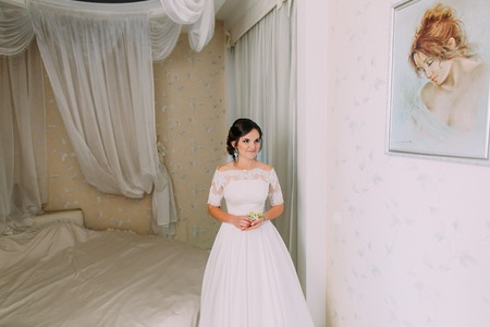 Beautiful bride is holding the little boutonniere and looking aside in the hotel room. Stok Fotoğraf - 108032293