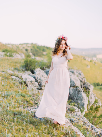 The bride is touching the curly hais and looking aside while standing on the mountains. Standard-Bild