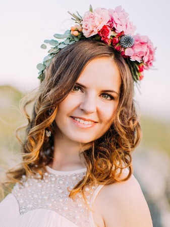 The close-up portrait of the smiling bride with the wreath of flowers on the head.
