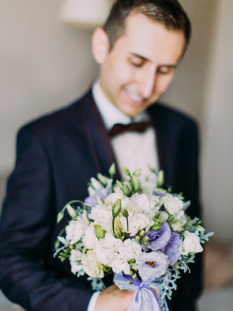 Close-up view of the huge wedding bouquet of white and purple roses at the blurred background of the groom.