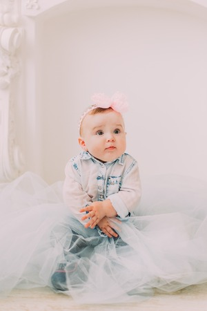 The portrait of the baby looking at the right side and sitting with the tulle on the floor. Standard-Bild