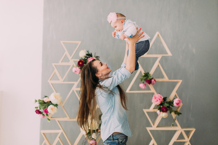 Woman is raising the smiling baby at the background of the wooden beams decorated with flowers.