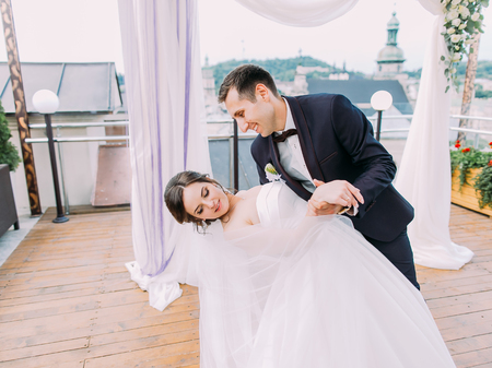 The horizontal view of the first dance of the newlywed couple on the open balcony.