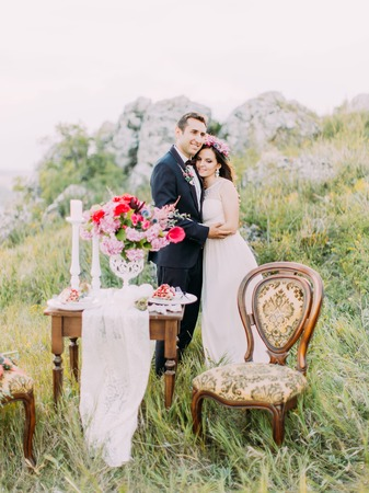 The cheerful newlywed couple is hugging behind the table set in the mountains.