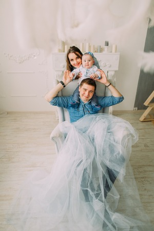 The father with the baby on his shoulder is sitting in the armshair while the mother is holding the hands of the kid.