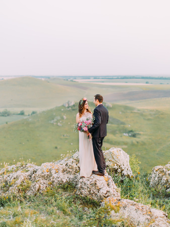 The happy newlyweds holding hands and the wedding bouquet at the background of the green mountains.