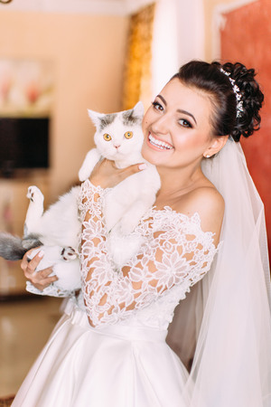 Half-length portrait of the smiling bride holding the white cat.