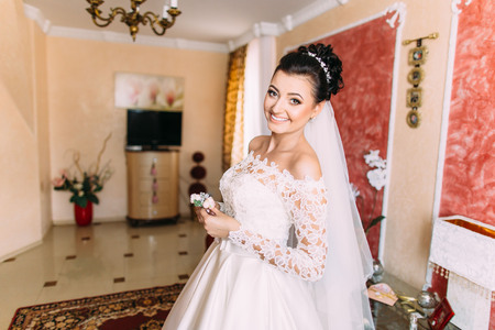 Horizontal portrait of the smiling bride holding the little boutonniere of roses.