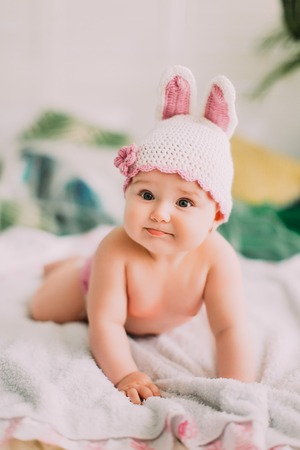The vertical portrait of the naked baby with the knitted hat lying on the white plaid.