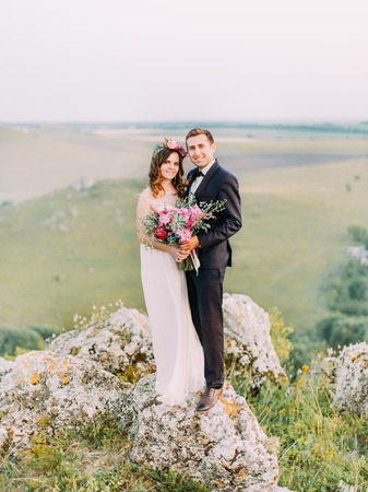 Full-length photo of the happy hugging newlyweds standing on the rocks. Banque d'images