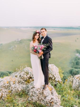 Full-length photo of the happy hugging newlyweds standing on the rocks. Standard-Bild