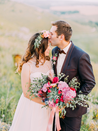 Half-length portrait of the groom kissing the bride in the forehead at the background of the mountains. Standard-Bild