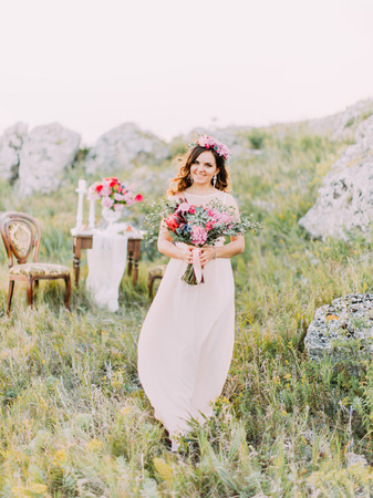 Cheerful bride with the bouquet. Full-length portrait in the mountains. Standard-Bild