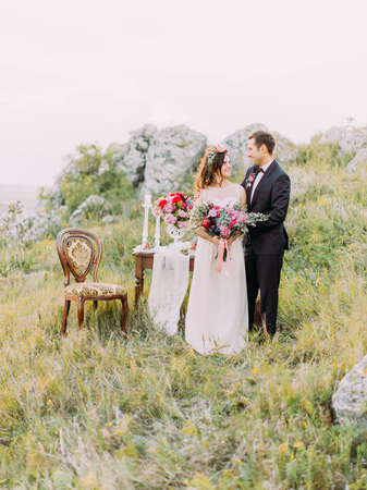 The smiling newlyweds standing near the table set in the mountains.