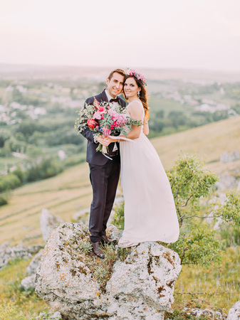 The happy newlyweds are hugging while standing head-to-head on the mountains. Full-length view. Standard-Bild