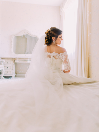 The back view of the lovely bride sitting on the bed.
