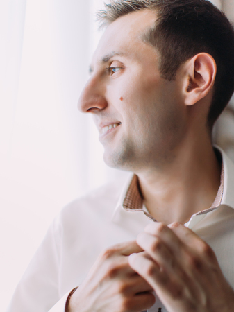 Close-up view of the groom buttoning his shirt and looking through window.