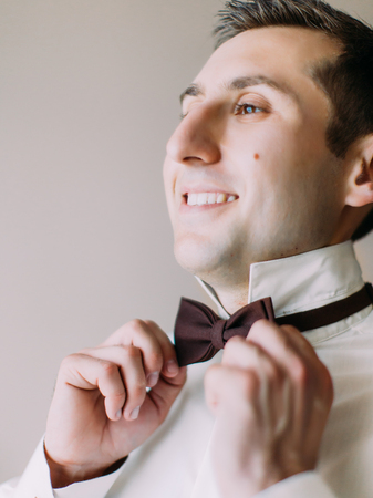 Side view of the smiling groom correcting the bow-tie. 版權商用圖片