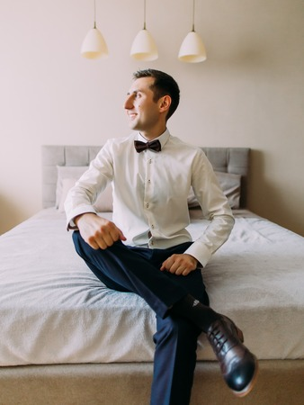 The vertical photo of the groom sitting leg on leg on the bed while looking through the window.