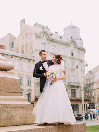 Full-length view of the groom hugging the bride back at the background of the city centre. Standard-Bild