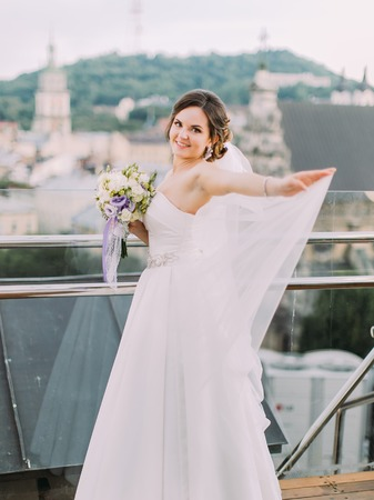 Smiling bride is correcting the veil while standing near the balcony fence.