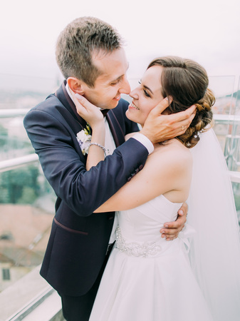The close-up sensitive portrait of the happy newlyweds touching the faces of each other.