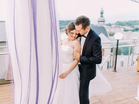 The sensitive portrait of the groom hugging the bride back on the balcony. Standard-Bild