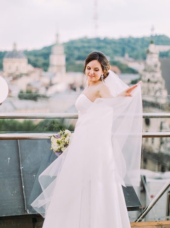 Beautiful bride is sorting the veil while standing near the balcony fence. Banque d'images
