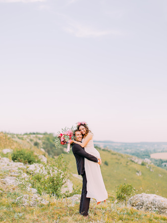 The full-length view of the groom carrying the bride in the mountains.