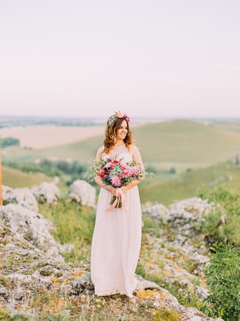 Beautiful bride with the huge wedding bouquet is looking aside while standing on the rocks.